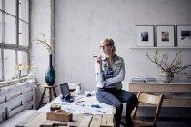 Женщина сидит на столе в лофте и смотрит в окно — стоковое фото