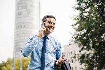Lächelnder Geschäftsmann am Handy im Stadtpark — Stockfoto