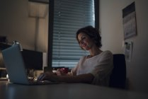 Businesswoman working overtime, using laptop in dark room and holding coffee cup — Stock Photo