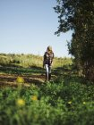 Agricultor feminino caminhando no campo de verão — Fotografia de Stock