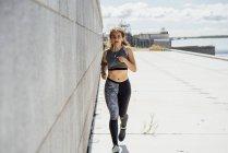 Jeune femme athlétique courant le long du mur — Photo de stock
