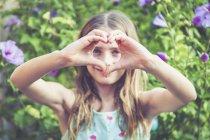 Giovane ragazza che fa una forma di cuore con le dita — Foto stock