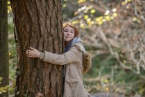 Portrait of smiling teenage girl hugging tree trunk in autumnal forest — Stock Photo