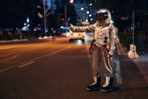 Spaceman standing on street in city at night and hitchhiking — Stock Photo