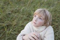 Білявий хлопчисько на лузі дивиться вгору. — стокове фото