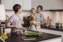 Счастливая лесбийская пара и их ребенок на кухне — стоковое фото