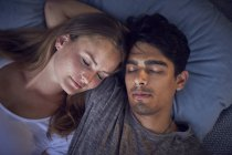 Young couple sleeping in bed, heads on on cushions — Stock Photo