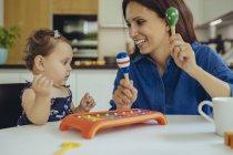 Filha feliz da matriz e do bebê que joga com chocalhos — Fotografia de Stock