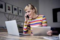 Retrato de la mujer sonriente en el teléfono usando el ordenador portátil y la tableta - foto de stock