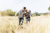 Happy family walking at riverside on sunny summer day — Stock Photo