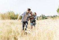 Felice famiglia passeggiando sul lungofiume nella soleggiata giornata estiva — Foto stock