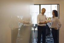 Бізнесмен тримає торт до дня народження в офісі, щаслива жінка дивиться на людину з рук на стегнах — стокове фото