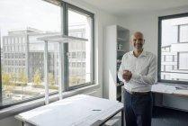 Улыбающийся бизнесмен, стоящий в своем кабинете за столом со строительным планом со скрепленными руками — стоковое фото