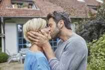 Couple kissing in front of their home — Stock Photo