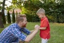 Père heureux avec son fils dans le jardin — Photo de stock