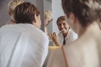 Lesbisches Paar und ihr kleiner Sohn bereiten sich auf ihren Tag im Badezimmer vor — Stockfoto