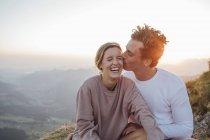 Suíça, Grosser Mythen, jovem casal feliz em uma viagem de caminhada tendo uma pausa ao nascer do sol — Fotografia de Stock