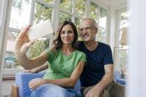 Улыбающаяся взрослая пара делает селфи дома — стоковое фото