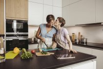 Happy lesbian couple in kitchen cooking together — Stock Photo