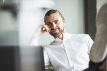 Retrato de homem de negócios sorridente sentado no escritório com os pés para cima — Fotografia de Stock