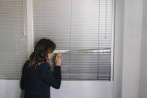 Femme debout par la fenêtre, espionnant à travers les stores — Photo de stock