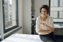 Imprenditrice seduta in ufficio, che lavora su progetti — Foto stock