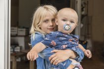 Portrait of girl holding baby boy brother at home — Stock Photo