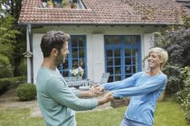 Happy couple dancing in front of their home — Stock Photo