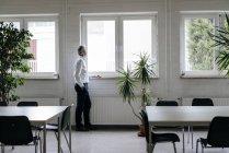 Empresario tomando un descanso, mirando por la ventana - foto de stock
