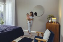 Smiling mother carrying her baby girl at home — Stock Photo