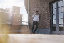 Бизнесмен, стоящий на террасе на крыше, делает телефонный звонок — стоковое фото