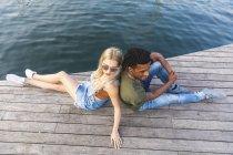 Multiculturale giovane coppia rilassante back to back sul molo — Foto stock