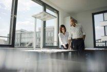 Due architetti che lavorano in ufficio, discutono di progetti alla finestra — Foto stock