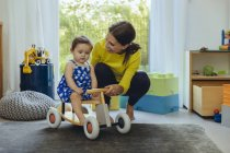Happy mother with baby daughter on toy car in living room — Stock Photo