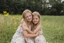 Two little sisters hugging each other on a meadow — Stock Photo