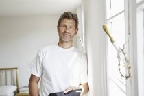 Uomo maturo in piedi alla finestra, tenendo tablet digitale — Foto stock