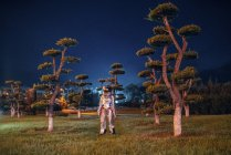Spaceman standing in illuminated park at night — Stock Photo
