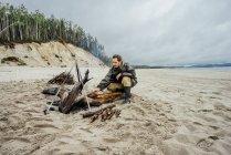 Homem coletando lenha na praia de areia, preparando fogueira — Fotografia de Stock