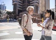 Літня пара стоячи на вулиці в місті і говорити — стокове фото