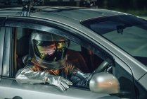 Close-up of spaceman sitting in car at night — Stock Photo