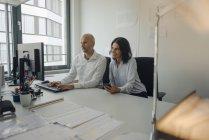 Homme d'affaires et femme travaillant ensemble dans le bureau au bureau avec ordinateur — Photo de stock