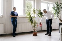 Manager watering plant in recreation room, while worker drinking coffee — Stock Photo