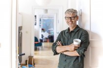 Portrait of smiling mature man with coffee cup leaning against door case at home — Stock Photo