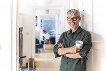 Porträt eines lächelnden, reifen Mannes mit Kaffeetasse, der zu Hause gegen die Türe gelehnt ist — Stockfoto