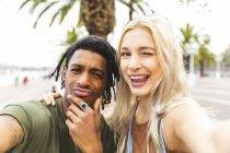 Портрет мультикультурной молодой пары, делающей селфи — стоковое фото