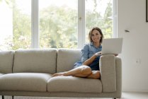 Sorrindo mulher madura sentada no sofá em casa com laptop — Fotografia de Stock
