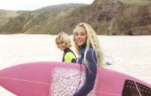 Портрет двух улыбающихся молодых серферов, гуляющих по пляжу — стоковое фото