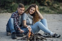 Romantic couple sitting at campfire in nature — Foto stock
