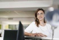 Empresaria esperando en recepción, luciendo soñadora - foto de stock
