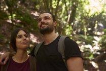 Усміхнена пара ходьба в лісі і дивиться навколо — стокове фото